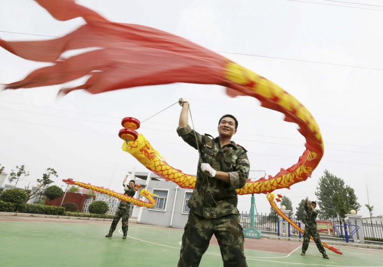 Paramilitary policemen rehearse for a diabolo performance ahead of China's Army Day, which falls on August 1, in Huaibei, Anhui province, July 27, 2014. (China Daily/Reuters)