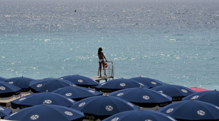 A woman sunbathes on a private beach during a sunny summer day in Nice, southeastern France, July 28, 2014. (Eric Gaillard/Reuters)