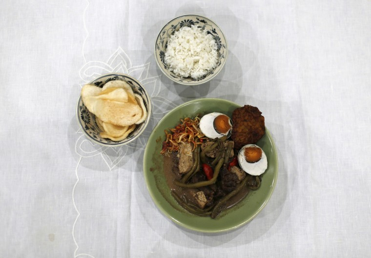 Brongkos, a Javanese dish made from oxtail, tofu, and red beans, which is usually eaten with crackers and rice is seen at Srikandi Hakim's house in Jakarta, July 17, 2014. During Ramadan, the ninth and holiest month in the Islamic calendar, Muslims refrain from eating and drinking during daylight hours. Reuters photographers took a series of portraits of Muslims observing Ramadan in different countries around the world, and asked them what food they liked to eat when breaking their daytime fast. Eid-al-Fitr, marking the end of Ramadan, will be celebrated at the beginning of next week. Picture taken July 17, 2014. (Beawiharta/Reuters)
