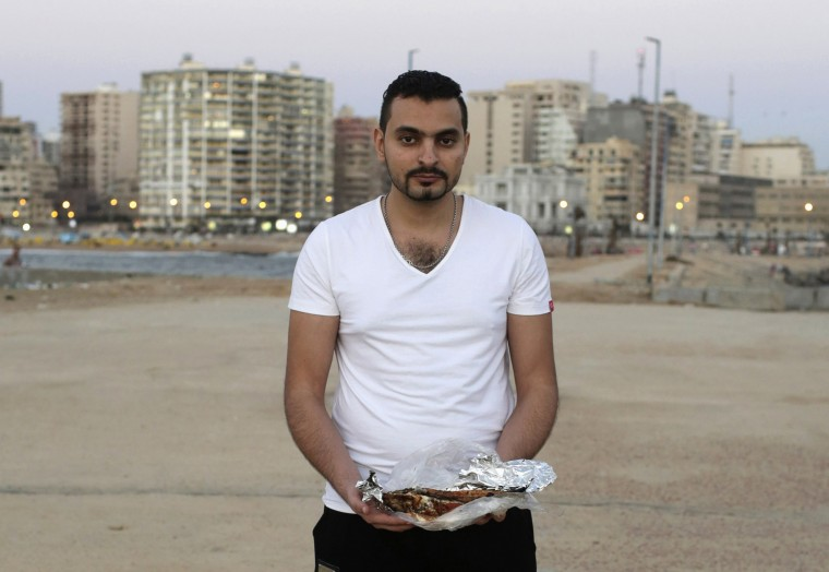 Hamed Mahmoud, 30, holds grilled fish as he poses for a photograph in Alexandria, Egypt, July 9, 2014. Mahmoud, from Cairo, said his favourite meal is grilled fish and seafood. While visiting Alexandria, he likes to eat with his friends by the sea. During Ramadan, the ninth and holiest month in the Islamic calendar, Muslims refrain from eating and drinking during daylight hours. Reuters photographers took a series of portraits of Muslims observing Ramadan in different countries around the world, and asked them what food they liked to eat when breaking their daytime fast. Eid-al-Fitr, marking the end of Ramadan, will be celebrated at the beginning of next week. Picture taken July 9, 2014. (Asmaa Waguih/Reuters)