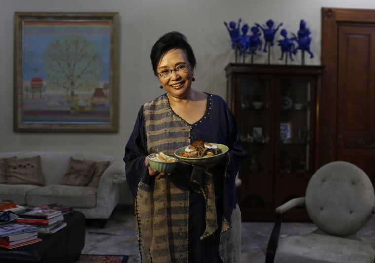 Srikandi Hakim, 69, holds a plate of brongkos, a Javanese dish made from oxtail, tofu, and red bean, as she poses for a photograph in Jakarta, July 17, 2014. During Ramadan, the ninth and holiest month in the Islamic calendar, Muslims refrain from eating and drinking during daylight hours. Reuters photographers took a series of portraits of Muslims observing Ramadan in different countries around the world, and asked them what food they liked to eat when breaking their daily fast. Eid-al-Fitr, marking the end of Ramadan, will be celebrated at the beginning of next week. Picture taken July 17, 2014. (Beawiharta/Reuters)