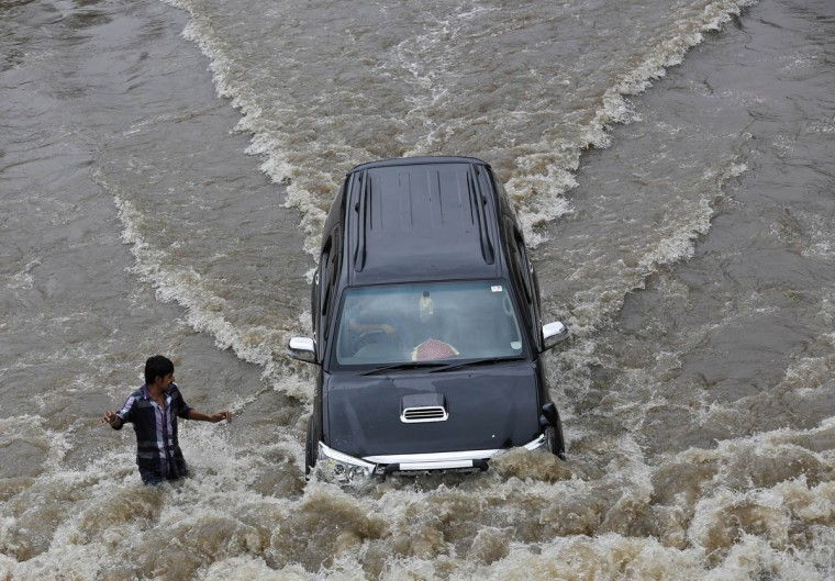 A car drives past a man through a flooded road after heavy monsoon rains in the western Indian city of Ahmedabad July 30, 2014. July, the second month of the monsoon season, usually gets the maximum rainfall, accounting for about a third of the seasonal downpour. (Amit Dave/Reuters photo)