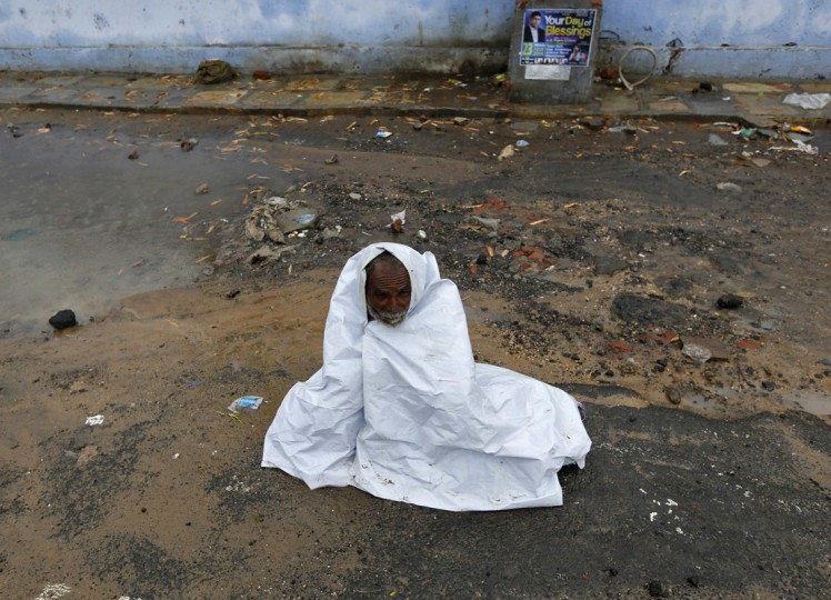 A man covers himself with a plastic to protect from rain in the western Indian city of Ahmedabad July 24, 2014. India's monsoon rains were 24 percent above average in the week ended July 23, the weather office said on Thursday, the first week of surplus rainfall during this year's monsoon season. (Amit Dave/Reuters)