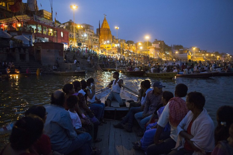 """Hindu devotees travel past holy ghats on the banks of the river Ganges in Varanasi, in the northern Indian state of Uttar Pradesh, June 16, 2014. The city of Varanasi, on the banks of the River Ganges, is widely considered Hinduism's holiest city and many Hindus believe that dying there and having their remains scattered in the Ganges allows their soul to escape a cycle of death and rebirth, attaining """"moksha"""" or salvation. """"Mukti Bhavan"""" or """"Salvation House"""", is a charity-run hostel that caters for people who wish to come to Varanasi to die. Guests can normally stay up to two weeks after which, if they haven't yet passed away, they are gently asked to leave. Picture taken June 16, 2014. (Danish Siddiqui/Reuters)"""