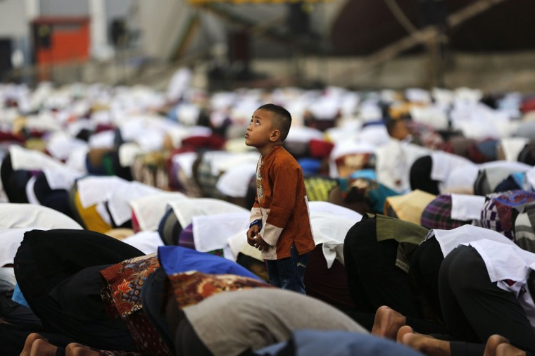A boy watches a remote-controlled camera fly above (unseen) during a prayer session on Eid al-Fitr at Sunda Kelapa port in Jakarta July 28, 2014. Indonesia, which has the world's largest Muslim population, celebrates Eid al-Fitr with mass prayers and family visits to mark the end of the Muslim holy fasting month of Ramadan. (Darren Whiteside/Reuters)