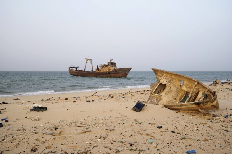 A decaying boat is seen docked off the port of Nouadhibou June 25, 2014. Mauritania's SNIM iron ore mining company aims to produce 13 million tonnes in 2014, around the same level as last year, the majority state-owned firm said. SNIM mines black iron ore in the northern town of Zouerate, a remote desert location which nevertheless attracts people from all over the country looking for work. SNIM employees proudly call their firm the lung of their nation's economy and the train that ferries the ore to the coast stretches some two kilometres, making it one of the world's longest. Picture taken June 25, 2014. REUTERS/Joe Penney