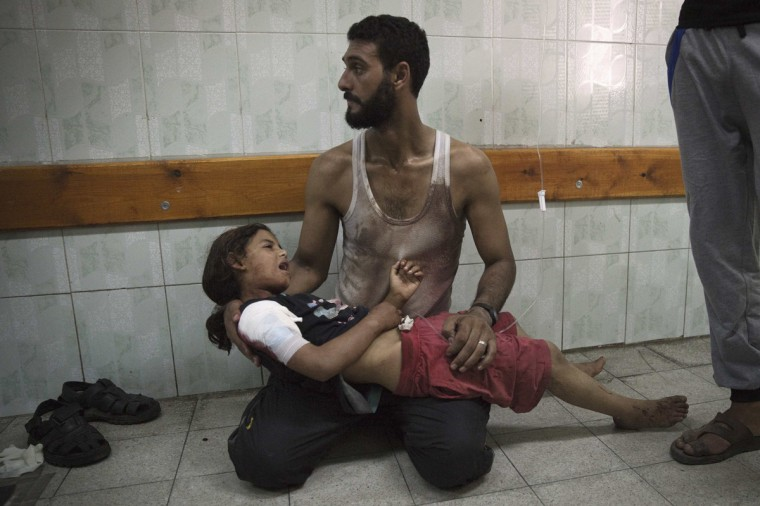 A Palestinian man holds a girl, whom medics said was injured in an Israeli shelling at a U.N-run school sheltering Palestinian refugees, at a hospital in the northern Gaza Strip July 24, 2014. At least 15 people were killed and many wounded on Thursday when Israeli forces shelled a U.N.-run school sheltering Palestinian refugees in northern Gaza, said a spokesman for the Gaza health ministry, Ashraf al-Qidra. Chris Gunness, spokesman for the main U.N. agency in Gaza UNRWA, confirmed the strike and criticised Israel. The Israel army had no immediate comment on the reports. Hamas fired rockets at Tel Aviv and said its gunmen carried out a lethal ambush on Israeli soldiers in north Gaza. (Finbarr O'Reilly /Reuters)