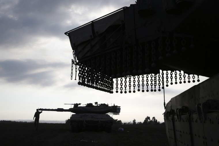 An Israeli soldier holds a weapon atop an armored personnel carrier (APC) after crossing back into Israel from Gaza July 28, 2014. Israel eased its assaults in the Gaza Strip and Palestinian rocket fire from the enclave declined sharply on Monday, the military said, with both the United States and United Nations calling for a durable ceasefire. (Baz Ratner/Reuters)