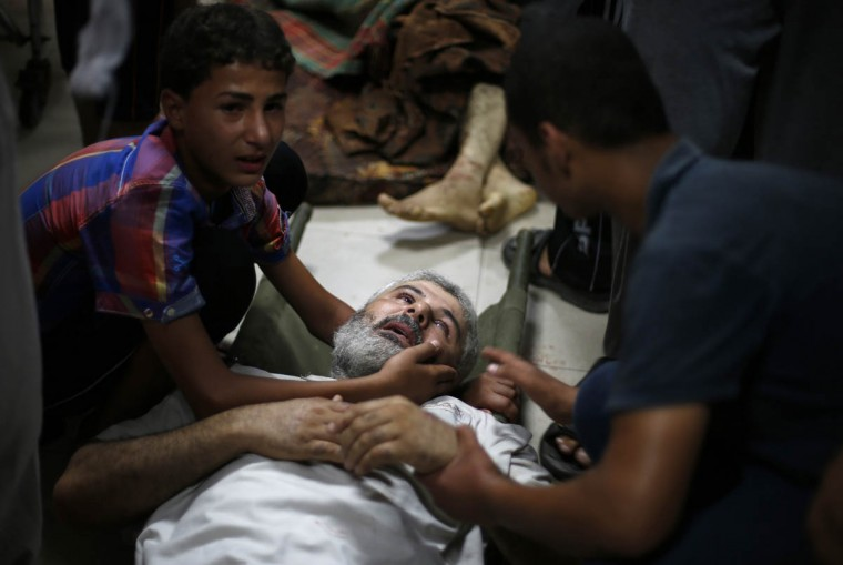 A Palestinian boy, left, comforts his father, whom medics said was wounded by Israeli shelling in Shejaia, at a hospital in Gaza City July 30, 2014. Israeli strikes near a market in the eastern Gaza Strip killed 15 Palestinians on Wednesday, the local health ministry said. Residents said that Israeli shelling and two missiles from the air hit the area in Shejaia, on the fringes of the city of Gaza. Ashraf al-Qidra, spokesman of the Gaza Health Ministry, said 160 people were also wounded. An Israeli military spokeswoman said she was checking the report. Israel launched its offensive in response to rocket salvos fired by Gaza's dominant Hamas Islamists and their allies. (Suhaib Salem/Reuters photo)