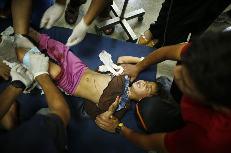 A Palestinian girl, whom medics said was wounded in Israeli shelling at a U.N-run school sheltering Palestinian refugees, is treated at a hospital in the northern Gaza Strip July 24, 2014. At least 15 people were killed and many wounded on Thursday when Israeli forces shelled a U.N.-run school sheltering Palestinian refugees in northern Gaza, said a spokesman for the Gaza health ministry, Ashraf al-Qidra. Chris Gunness, spokesman for the main U.N. agency in Gaza UNRWA, confirmed the strike and criticised Israel. The Israel army had no immediate comment on the reports. Hamas fired rockets at Tel Aviv and said its gunmen carried out a lethal ambush on Israeli soldiers in north Gaza. (Mohammed Salem/Reuters)