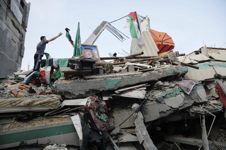 A Palestinian man throws a flag atop the rubble of the home of Hamas Gaza leader Ismail Haniyeh, which Gaza's interior ministry said was hit by a missile fired by Israeli aircraft before dawn on Tuesday, causing damage but no casualties, in Gaza City July 29, 2014. Israel's military pounded targets in the Gaza Strip on Tuesday after Prime Minister Benjamin Netanyahu said his country needed to be prepared for a long conflict in the Palestinian enclave, squashing any hopes of a swift end to 22 days of fighting. Israel launched its Gaza offensive on July 8, saying its aim was to halt rocket attacks by Hamas and its allies. It later ordered a land invasion to find and destroy the warren of Hamas tunnels that crisscrosses the border area. Some 1,087 Gazans, most of them civilians, have died in the 22-day-old conflagration. Israel has lost 48 soldiers and another three civilians have been killed by Palestinian shelling. (REUTERS/Finbarr O'Reilly)