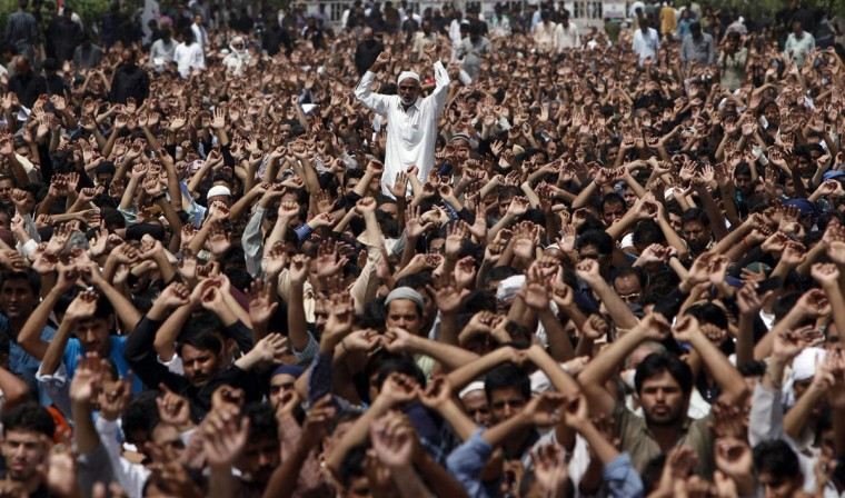 Shi'ite Muslim men chant slogans as they take part in a religious procession of Yaum-e-Ali, marking the death anniversary of Imam Ali Ibn Abu Talib, son-in-law of Prophet Mohammad, in Karachi July 20, 2014. Imam Ali, the son-in-law and cousin of Prophet Mohammad, was wounded in the head during a battle and died after two days in 661 AD in Najaf. (REUTERS/Akhtar Soomro)