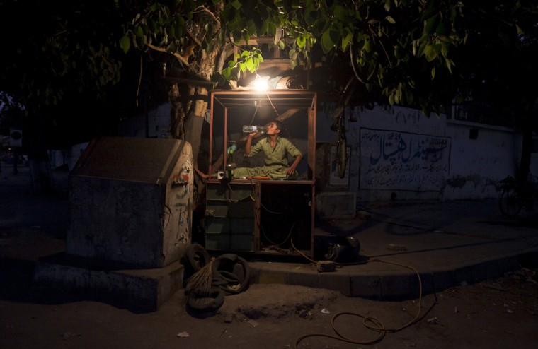 A boy, who repair tires, drinks water after breaking his fast on his makeshift stall, during the holy fasting month of Ramadan in Karachi July 17, 2014. (Akhtar Soomro/Reuters)
