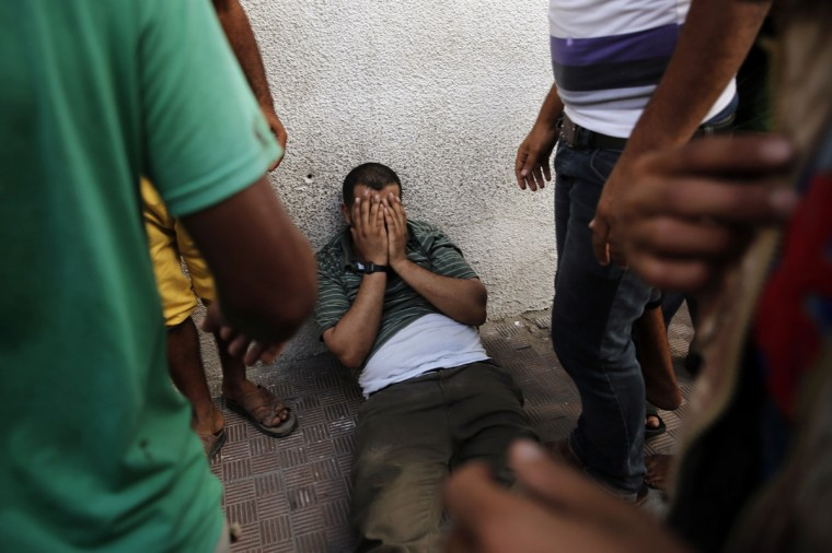 The father of two boys from the Shaibar family, whom medics said were killed along with a girl from the same extended family by an Israeli air strike after the end of a five-hour humanitarian ceasefire, grieves outside the morgue in Gaza City July 17, 2014. Palestinians rushed to shops and banks on Thursday during the five-hour humanitarian ceasefire that largely held, and an Israeli official said Egypt had proposed a permanent truce that would start on Friday. Gaza health officials say at least 224 Palestinians, mostly civilians, have been killed in 10 days of warfare between the Islamist Hamas rulers of Gaza and Israel. In Israel, one civilian has been killed by fire from Gaza, where the Israeli military says more than 1,300 rockets have been launched into the Jewish state. (Finbarr O'Reilly/Reuters)