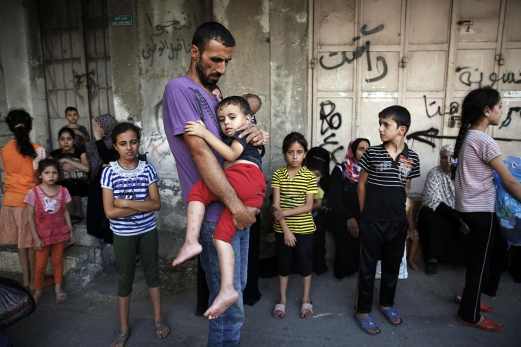 A Palestinian man holds a child while fleeing the Shujayeh neighborhood during heavy Israeli shelling in Gaza City July 20, 2014. Israel said on Sunday it had expanded its ground offensive in Gaza and militants kept up rocket fire into the Jewish state with no sign of a diplomatic breakthrough to end the worst fighting between Israel and Hamas in two years. Gaza residents said land and naval shellings were the heaviest in 13 days of fighting. Explosions rocked the coastal enclave overnight and shells fired by Israeli naval forces lit up the sky. (Finbarr O'Reilly/Reuters)
