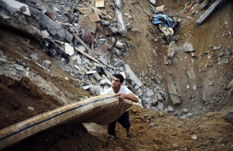 A Palestinian salvages a mattress from the remains of a house, which police said was destroyed in an Israeli air strike, in Khan Younis in the southern Gaza Strip July 21, 2014. Israeli tanks shelled militant targets in the Gaza Strip on Monday and a woman died in an air strike after the bloodiest day of a nearly two-week military offensive that showed no signs of abating, despite global calls for a truce. Palestinian health officials said the death toll since July 8 had reached 447, including many civilians, with a woman killed in the predawn strike in Beit Hanoun and 12 more bodies recovered from the embattled Shejaia neighbourhood where the number of fatalities rose to 72 from Sunday's fighting. Israel's army said it had been targeting militants from Gaza's dominant Hamas group, charging that they fired rockets from Shejaia and built tunnels and command centres there. The army said it had warned civilians to leave two days earlier. (REUTERS/Ibraheem Abu Mustafa)