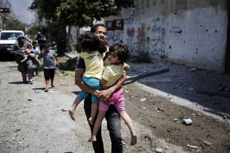 A Palestinian man carries children in the Shejaia neighborhood, which was heavily shelled by Israel during fighting, in Gaza City July 20, 2014. At least 50 Palestinians were killed on Sunday by Israeli shelling in a Gaza neighborhood, where bodies were strewn in the street and thousands fled for shelter to a hospital packed with wounded, witnesses and health officials said. Militants kept up their rocket fire on Israel, with no sign of a diplomatic breakthrough toward a ceasefire in sight. (Finbarr O'Reilly/Reuters)