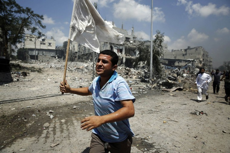 A Palestinian man runs with a white flag in the Shejaia neighborhood, which was heavily shelled by Israel during fighting, in Gaza City July 20, 2014. At least 50 Palestinians were killed on Sunday by Israeli shelling in the Gaza neighborhood, where bodies were strewn in the street and thousands fled for shelter to a hospital packed with wounded, witnesses and health officials said. Militants kept up their rocket fire on Israel, with no sign of a diplomatic breakthrough toward a ceasefire in sight. (Finbarr O'Reilly/Reuters)