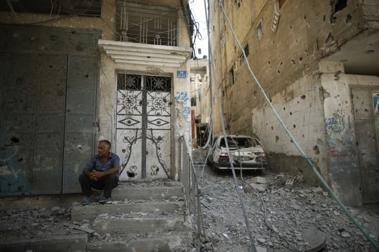 A Palestinian man sits outside his house in the Shejaia neighborhood which was heavily shelled by Israel during fighting in Gaza City July 20, 2014. At least 50 Palestinians were killed on Sunday by Israeli shelling in the Gaza neighborhood, where bodies were strewn in the street and thousands fled for shelter to a hospital packed with wounded, witnesses and health officials said. Militants kept up their rocket fire on Israel, with no sign of a diplomatic breakthrough toward a ceasefire in sight. (Mohammed Salem/Reuters)