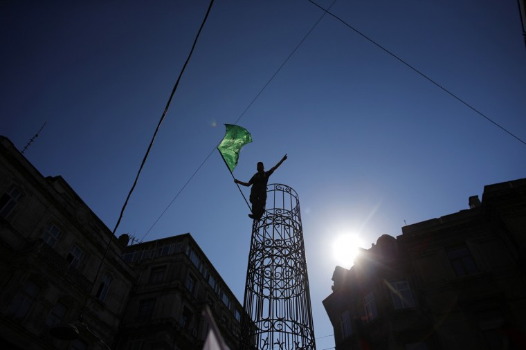 """A demonstrator holds up an Islamic flag that reads, """"There is no god but Allah. Mohammed is his prophet"""", as he takes part in a protest against Israel's military action in Gaza, in Istanbul July 17, 2014. Israeli leaders on Thursday played down prospects of a permanent Gaza ceasefire and fighting returned to a familiar pattern of Palestinian rocket salvoes and Israeli bombing after a five-hour humanitarian truce. (Murad Sezer/Reuters)"""