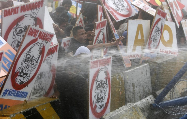 Protesters react as they are hosed by a water cannon as Philippine President Benigno Aquino delivers his fifth State of the Nation Address (SONA) during the joint session of the 16th Congress at the House of Representatives of the Philippines in Quezon city, Metro Manila July 28, 2014. The biggest political crisis that Aquino has faced in four years in power could damage his image as a crusader against corruption and undermine his ability to deliver on reforms to sustain strong economic growth. The Supreme Court this month declared partly illegal a 145 billion pesos ($3.34 billion) economic stimulus fund that Aquino created in 2011 from budget savings, sparking a storm of controversy that has distracted the government from its work. (Al Falcon/Reuters)