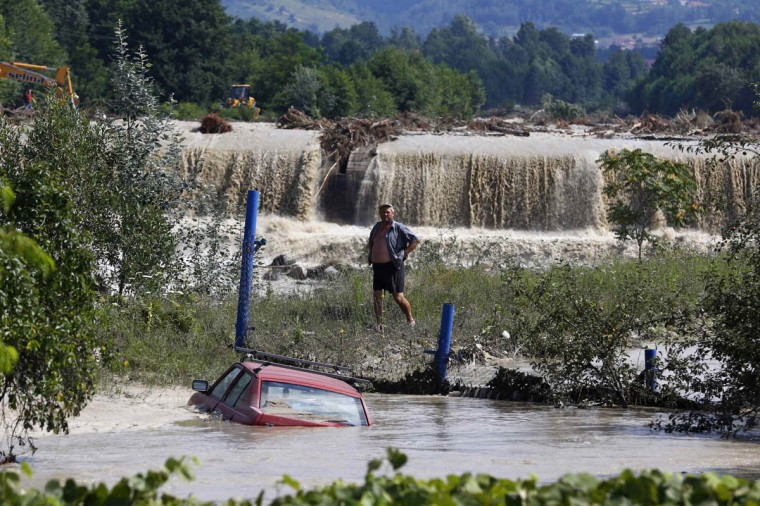 A man looks at a car that is partially submerged in floodwaters in Novaci, southwest Romania, July 30, 2014. Hundreds of people were evacuated from floods in southern Romania, local authorities reported. (Bogdan Cristel/Reuters photo)