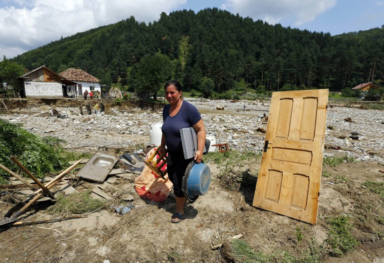 A woman carries her belongings after her house was destroyed by flash floods in Vaideeni, southern Romania, July 30, 2014. Hundreds of people were evacuated from floods in southern Romania, local authorities reported. (Bogdan Cristel/Reuters photo)