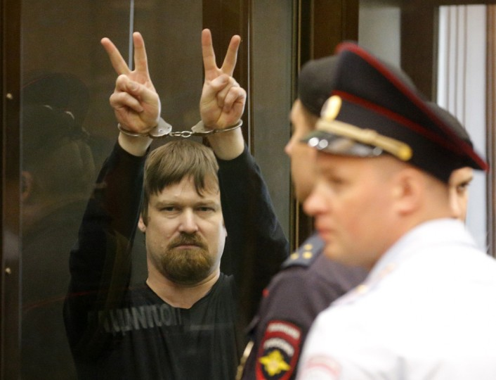 Leonid Razvozhayev, co-defendant of opposition leader Sergei Udaltsov, gestures from the defendants cage during a court hearing in Moscow July 24, 2014. Udaltsov and Razvozhayev are charged with the organization of riots and use of violence against police during a protest rally in Moscow's Bolotnaya Square on May 6, 2012, the eve of Russian President Vladimir Putin's inauguration, according to local media. (Maxim Shemetov/Reuters)