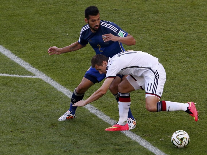 Argentina's Ezequiel Garay (L) fights for the ball against Germany's Miroslav Klose during their 2014 World Cup final at the Maracana stadium in Rio de Janeiro July 13, 2014. (David Gray/Reuters)