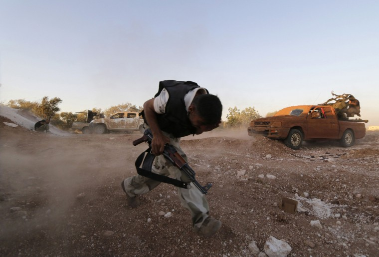 A Free Syrian Army fighter runs while holding a weapon in Wadi Al-Dayf in the southern Idlib countryside July 16, 2014. Picture taken July 16, 2014. (Khalil Ashawi/Reuters)