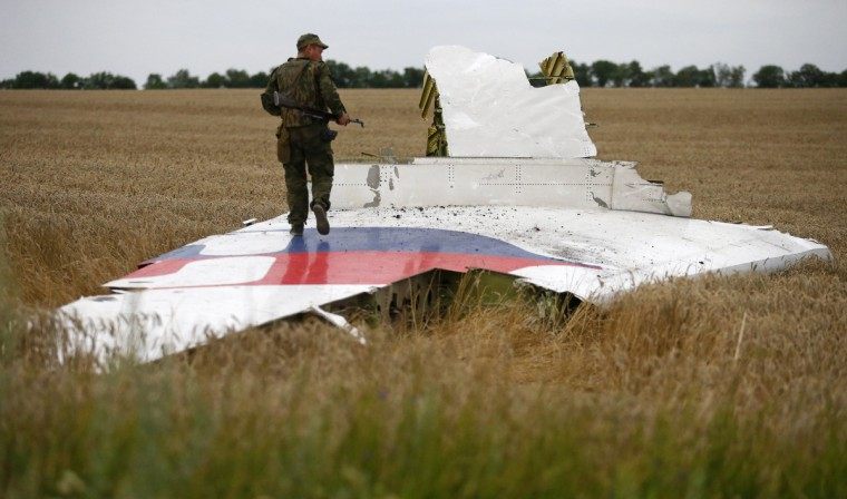 An armed pro-Russian separatist stands on part of the wreckage of the Malaysia Airlines Boeing 777 plane after it crashed near the settlement of Grabovo in the Donetsk region, July 17, 2014. The Malaysian airliner flight MH-17 was brought down over eastern Ukraine on Thursday, killing all 295 people aboard and sharply raising stakes in a conflict between Kiev and pro-Moscow rebels in which Russia and the West back opposing sides. (Maxim Zmeyev/Reuters)