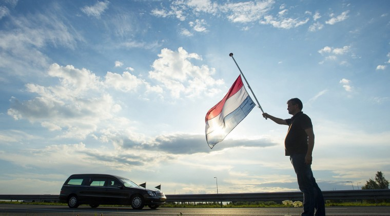 Dutch Ronald Visee holds a Netherlands flag flying at half-mast (R) as a hearse carrying the remains of victims of the Malaysia Airlines flight MH17 plane disaster are escorted on highway A27 near Nieuwegein by military police, on their way to be identified by forensic experts in Hilversum, July 24, 2014. (Toussaint Kluiters/United Photos/Reuters)