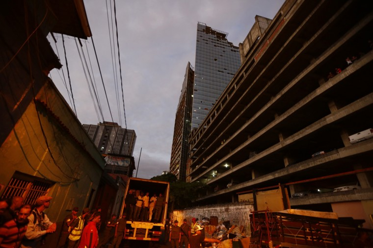 "People load trucks with the belongings of evicted Tower of David (in the background) residents in Caracas July 22, 2014. Venezuelan soldiers and officials began moving hundreds of families on Tuesday out of a half-built 45-story skyscraper that dominates the Caracas skyline and is thought to be the tallest slum in the world. The mass eviction from the ""Tower of David"", originally intended to be a bank center but abandoned since 1994 and later home to some 3,000 needy Venezuelans, proceeded peacefully. (Jorge Silva/Reuters)"