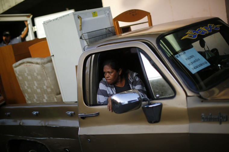 "An evicted resident of Tower of David sits in a pick-up truck as belongings are transferred to a bigger vehicle in Caracas July 22, 2014. Venezuelan soldiers and officials began moving hundreds of families on Tuesday out of a half-built 45-story skyscraper that dominates the Caracas skyline and is thought to be the tallest slum in the world. The mass eviction from the ""Tower of David"", originally intended to be a bank center but abandoned since 1994 and later home to some 3,000 needy Venezuelans, proceeded peacefully. (Jorge Silva/Reuters)"