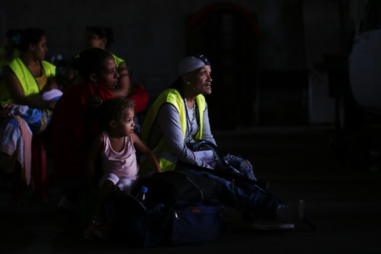 "Evicted residents of Tower of David wait for a bus to transport them to their new homes in Caracas July 22, 2014. Venezuelan soldiers and officials began moving hundreds of families on Tuesday out of a half-built 45-story skyscraper that dominates the Caracas skyline and is thought to be the tallest slum in the world. The mass eviction from the ""Tower of David"", originally intended to be a bank center but abandoned since 1994 and later home to some 3,000 needy Venezuelans, proceeded peacefully. (Jorge Silva/Reuters)"