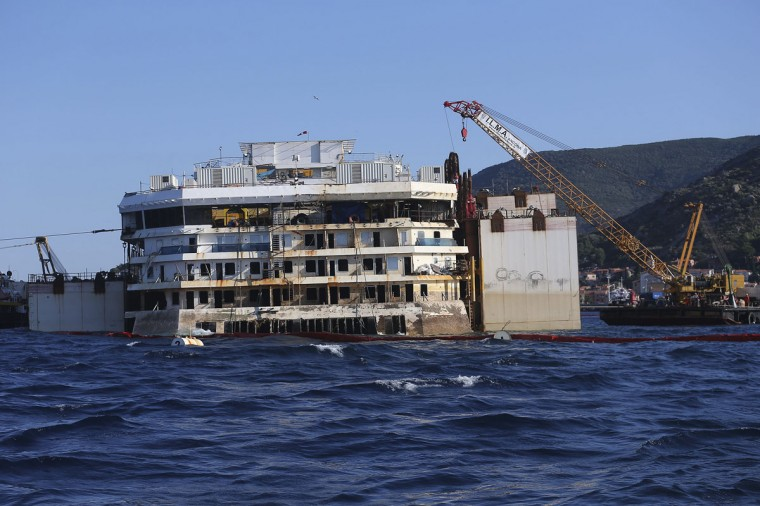 The rear of the cruise liner Costa Concordia is pictured at Giglio harbor at Giglio Island July 15, 2014. Engineers were securing the final chains to the Costa Concordia on Tuesday, preparing the wrecked luxury liner to be towed away from the Italian island where it sank two and half years ago, killing 32 people. (REUTERS/Alessandro Bianchi)