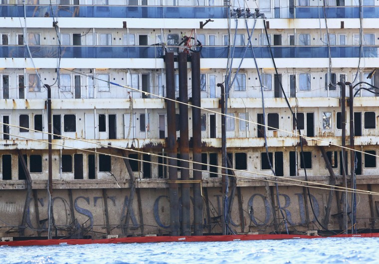 The sign of the Costa Concordia cruise liner is seen as it emerges during the refloat operation at Giglio harbor at Giglio Island July 19, 2014. (REUTERS/Alessandro Bianchi)
