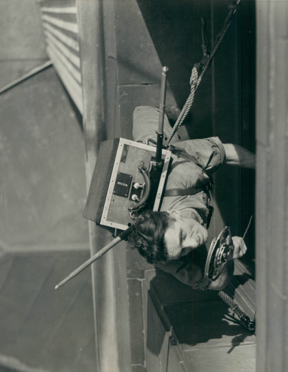 From Chicago to New York: Alex Henderson, window washer at the Merchandise Mart in Chicago, talks in a microphone to a brother window washer at the Empire State Building in NYC. The radio conversation was arranged by the National Broadcasting Company as the Chicago window washer and the NYC washer touted their trade.