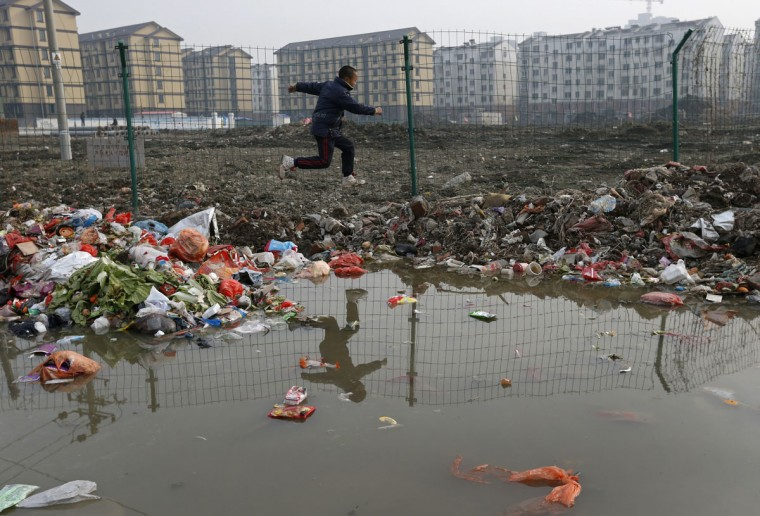 A child is reflected in a drainage ditch as he jumps over trash at a village which will soon be demolished, on the outskirts of Jiaxing city, Zhejiang province, January 12, 2013. (REUTERS/William Hong)