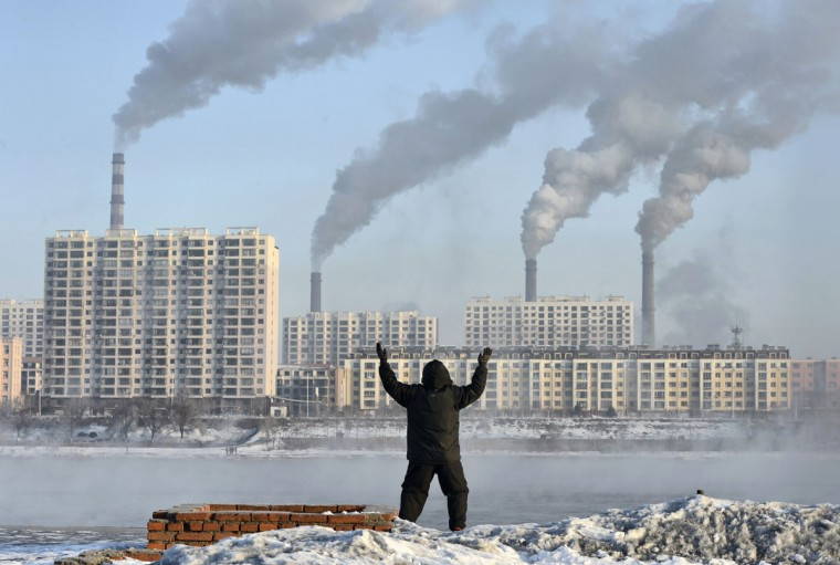An elderly man exercises in the morning as he faces chimneys emitting smoke behind buildings across the Songhua river in Jilin, Jilin province, February 24, 2013. China's new rulers will focus on consumer-led growth to narrow the gap between rich and poor while taking steps to curb pollution and graft, the government said on Tuesday, tackling the main triggers for social unrest in the giant nation. (REUTERS/Stringer)