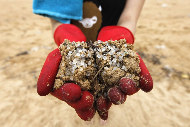 A volunteer holds sand mixed with plastic pellets during a clean-up of a beach during Hong Kong's Discovery Day on August 4, 2012.The Government says it has so far collected more than 58,000 kilograms (177,868 pounds) of plastic pellets after several containers were blown off a ship when Typhoon Vicente hit Hong Kong at the end of last month. (REUTERS/Tyrone Siu)