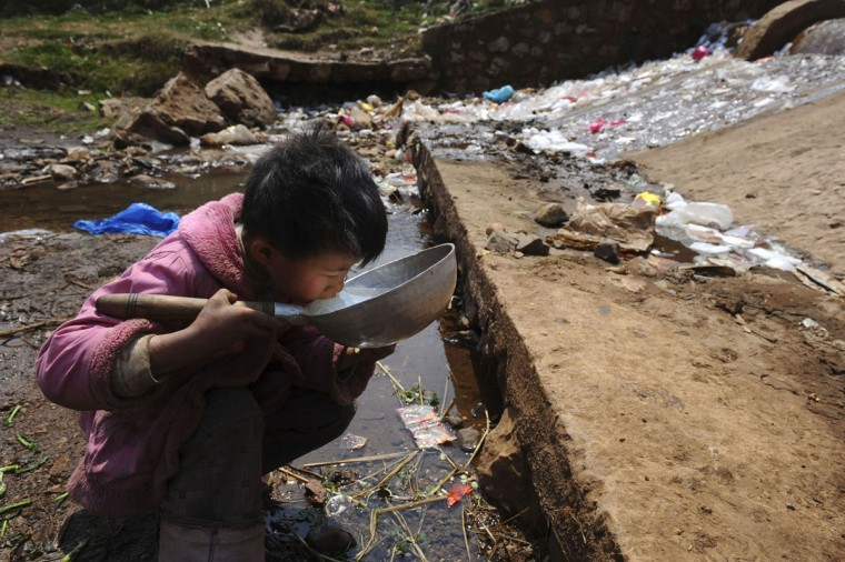 A child drinks water near a stream in Fuyuan county, Yunnan province on March 20, 2009. (REUTERS/Stringer)