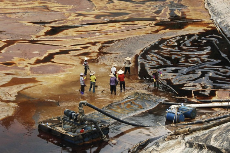 Laborers work to drain sewage water from a leaked sewage tank at a copper mine in Shanghang, Fujian province, July 13, 2010. The sewage leak from the copper mine owned by Zijin Mining Group Co, whose shares were suspended from trading in Hong Kong on Monday, has polluted a river and reservoir in Fujian province, Xinhua news agency reported. (REUTERS/Stringer)