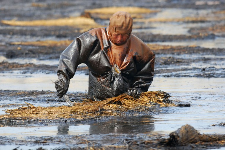 A laborer cleans up oil at the oil spill site near Dalian port, Liaoning province July 23, 2010. (REUTERS/Stringer)