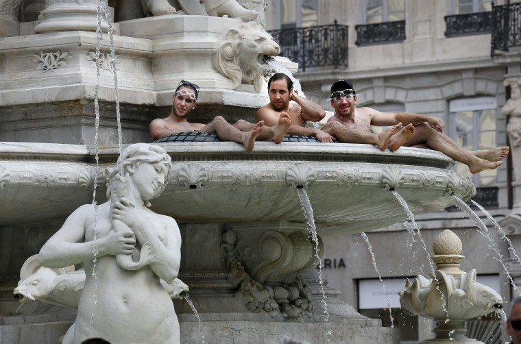 Three men sit and cool off in a fountain in the center of Lyon. (Robert Pratta/Reuters)