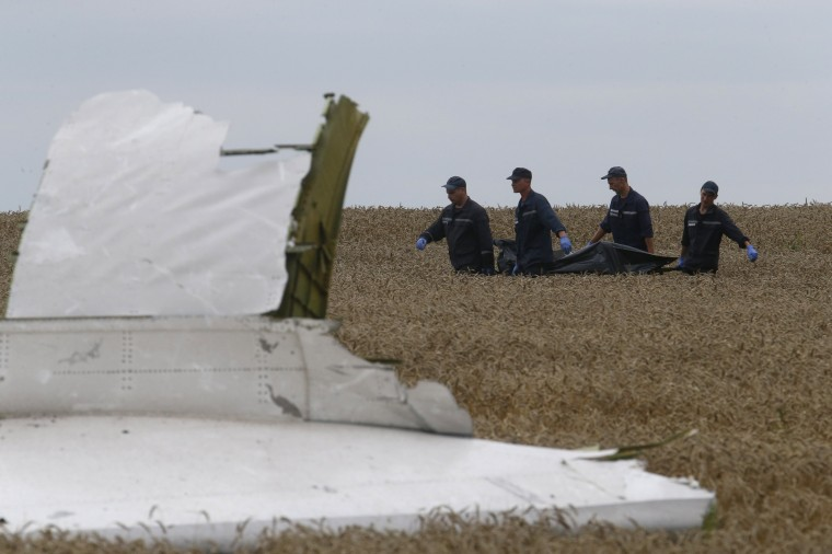 Members of the Ukrainian Emergency Ministry carry a body at the crash site of Malaysia Airlines Flight MH17, near the settlement of Grabovo in the Donetsk region. Russia called on Ukraine's authorities and rebels on Saturday to give international experts access to the crash site of the Malaysian Airlines Boeing 777 plane, the foreign ministry said. (Maxim Zmeyev/Reuters)