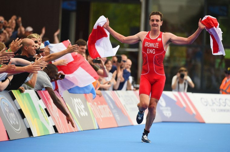 Alistair Brownlee of England celebrates as he reaches the finish line to win gold in the Triathlon Mixed Teams Relay Final at Strathclyde Country Park during day three of the Glasgow 2014 Commonwealth Games in Glasgow, Scotland. (Jeff J Mitchell/Getty Images)