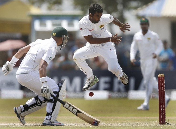 Sri Lanka's Dilruwan Perera jumps away from the ball as South Africa's Alviro Petersen (L) completes his run during the fourth day of their first test cricket match in Galle. (Dinuka Liyanawatte/Reuters)