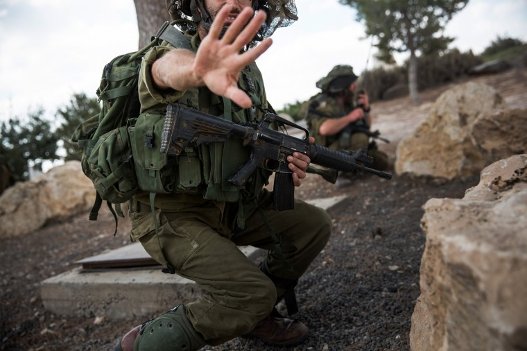 "A soldier motions that he does not want his photo taken while on an operation near the Israeli-Gaza border near Sderot, Israel. As operation ""Protective Edge"" enters it's 12th day, over 300 Gazans have been killed along with three Israeli soldiers. (Andrew Burton/Getty Images)"