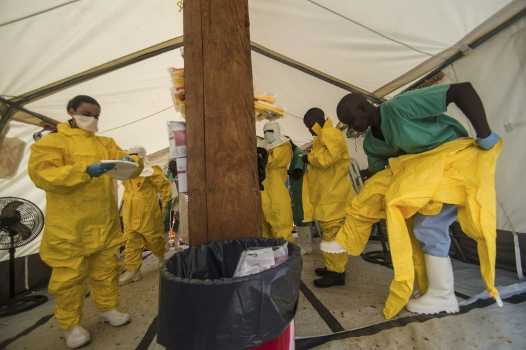 Medical staff working with Medecins sans Frontieres (MSF) put on their protective gear before entering an isolation area at the MSF Ebola treatment centre in Kailahun on July 20, 2014. (REUTERS/Tommy Trenchard)